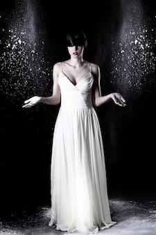 Mooie vrouw in witte jurk en vliegende stof