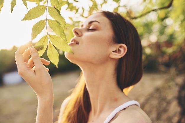 Mooie vrouw in witte jurk in de buurt van boom natuur groene bladeren