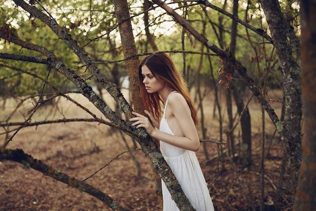 Mooie vrouw in witte jurk leunde op een boomstam op de natuur in het bos