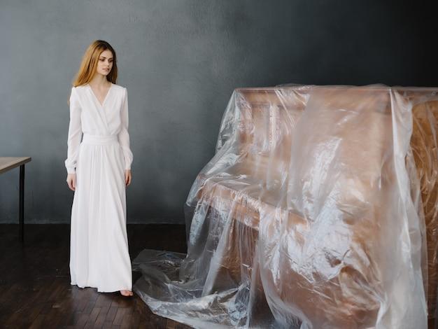 Mooie vrouw in witte jurk leunend op de piano poseren luxe