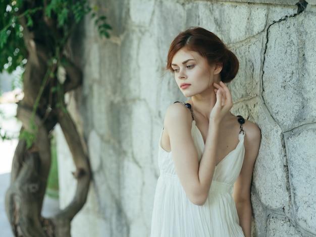 Mooie vrouw in witte jurk poseren in de natuur in de buurt van een boom griekenland