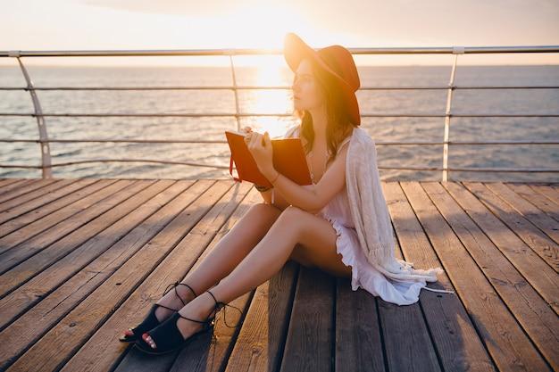 Mooie vrouw in witte jurk zittend aan zee op zonsopgang denken en maken van aantekeningen in dagboekboek