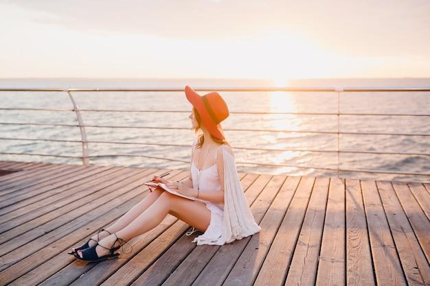 Mooie vrouw in witte jurk zittend aan zee op zonsopgang denken en notities maken
