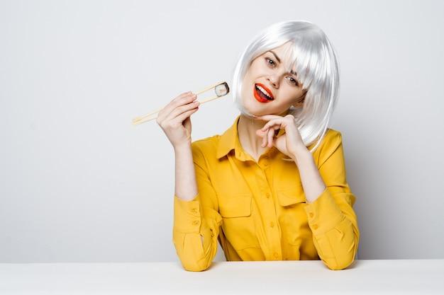 Mooie vrouw in witte pruik zittend aan tafel en glamour sushi eten