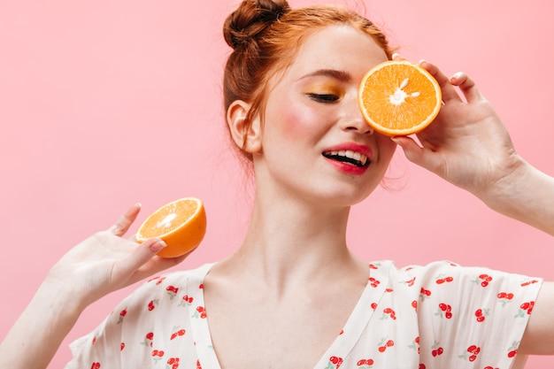 Mooie vrouw in witte top met kersenprint poseren met sinaasappels op geïsoleerde achtergrond.