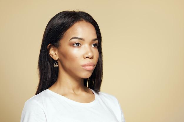 Mooie vrouw in witte tshirt afrikaanse uitstraling cosmetica beige achtergrond