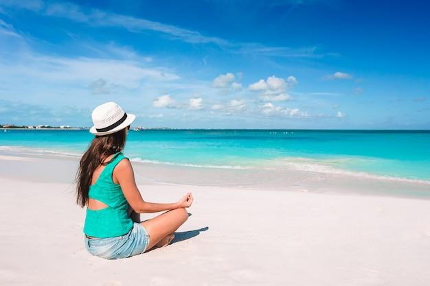 Mooie vrouw in yoga-positie tijdens tropische vakantie