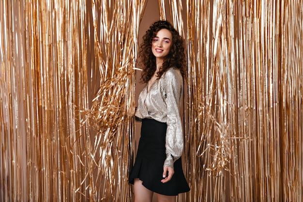 Mooie vrouw in zilveren outfit onderzoekt camera op gouden achtergrond