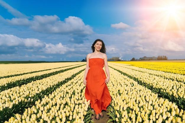 Mooie vrouw in zomerjurk die staat in kleurrijke tulpenvelden in amsterdam, holland