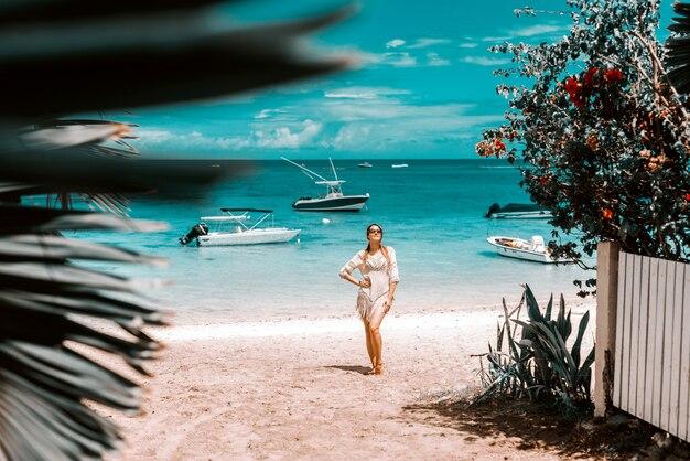 Mooie vrouw in zomerjurk poseren op het strand.