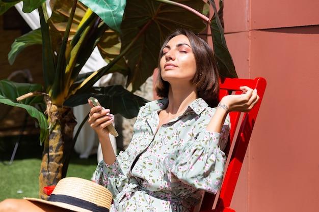 Mooie vrouw in zomerjurk zit op een stoel in de achtertuin op zonnige dag met mobiele telefoon