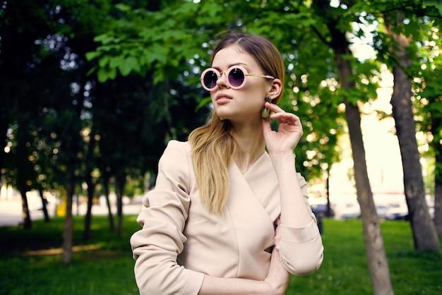 Mooie vrouw in zonnebril buiten in groene bomen park reizen