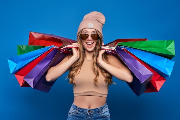 Mooie vrouw in zonnebril en een hoed met pakketten in de uitverkoop