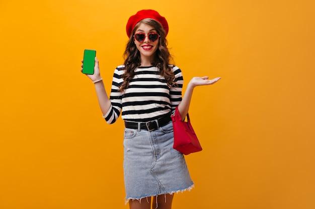 Mooie vrouw in zonnebril en rode baret toont smartphone. aantrekkelijk meisje in denimrok met brede zwarte band die op geïsoleerde achtergrond glimlacht.