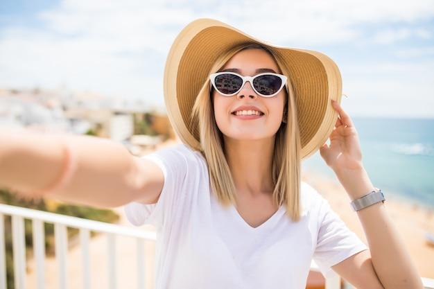 Mooie vrouw in zonnebril en zomerhoed die selfie op strand nemen