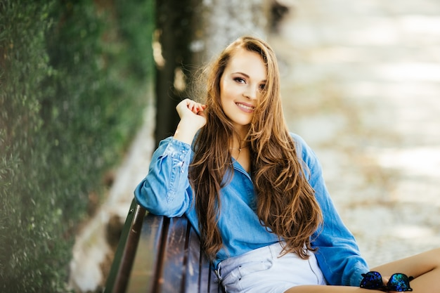 Mooie vrouw in zonnebril glimlach ontspannen op bankje in het park