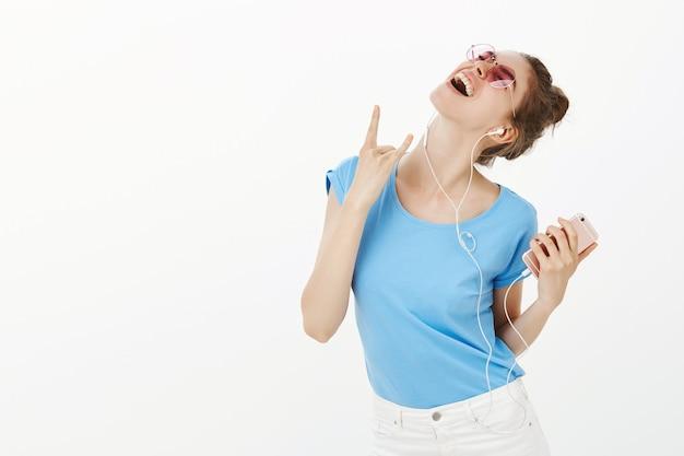 Mooie vrouw in zonnebril luisteren muziek in oortelefoons, met behulp van mobiele telefoon