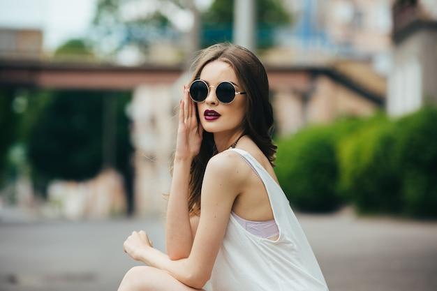 Mooie vrouw in zonnebril zittend op het asfalt