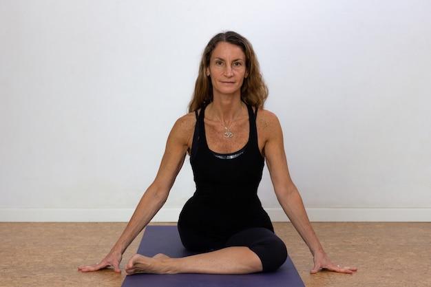 Mooie vrouw in zwaan pose op mat op witte achtergrond slanke vrouwelijke yogi op overall doet yoga