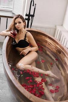 Mooie vrouw in zwart ondergoed rusten in de badkamer. een verliefde vrouw rust, bloemen en rozenblaadjes