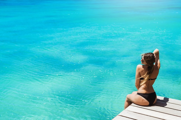 Mooie vrouw in zwarte bikini zonnebaden genieten van prachtig uitzicht op de oceaan