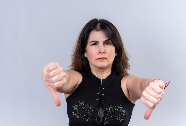 Mooie vrouw in zwarte blouse die ongelukkig duimen naar beneden doet