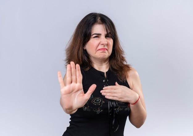 Mooie vrouw in zwarte blouse die ontevreden toont dat ze iets niet leuk vindt