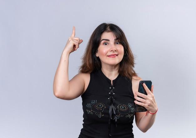Mooie vrouw in zwarte blouse gelukkig voor het krijgen van een nieuw idee