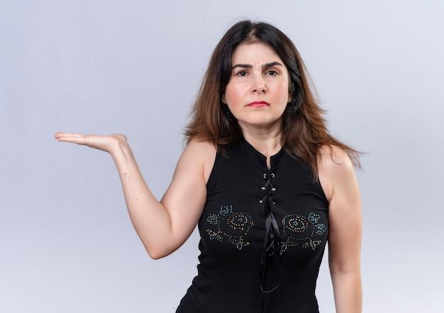 Mooie vrouw in zwarte blouse lookin camera weet niet wat te doen