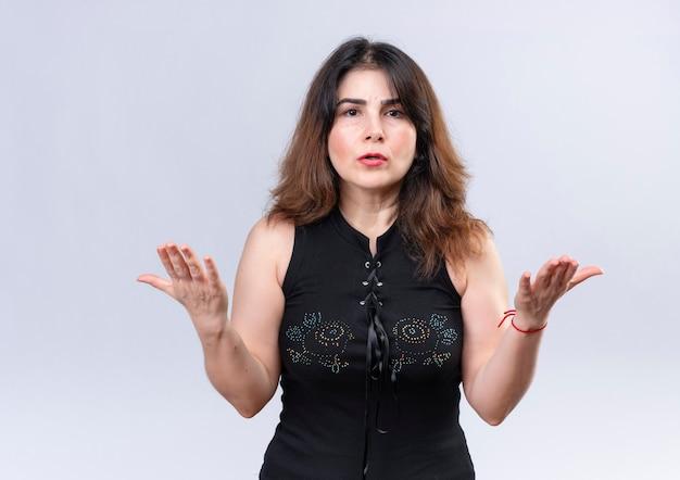Mooie vrouw in zwarte blouse op zoek angstig weet niet wat ze moet doen