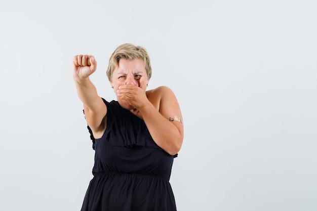 Mooie vrouw in zwarte blouse toont haar kracht met opgeheven arm terwijl ze hand op mond houdt en boos kijkt