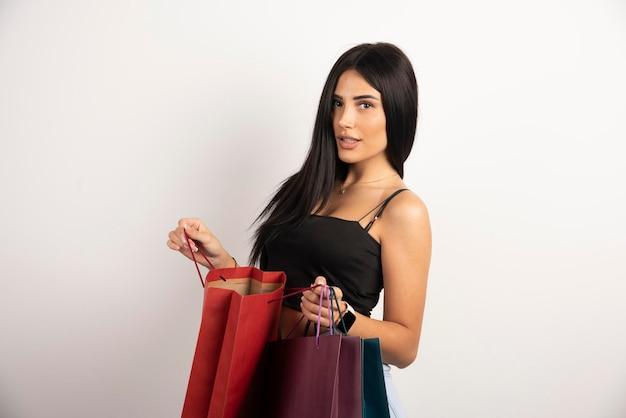 Mooie vrouw in zwarte bovenkant die boodschappentassen openen. hoge kwaliteit foto