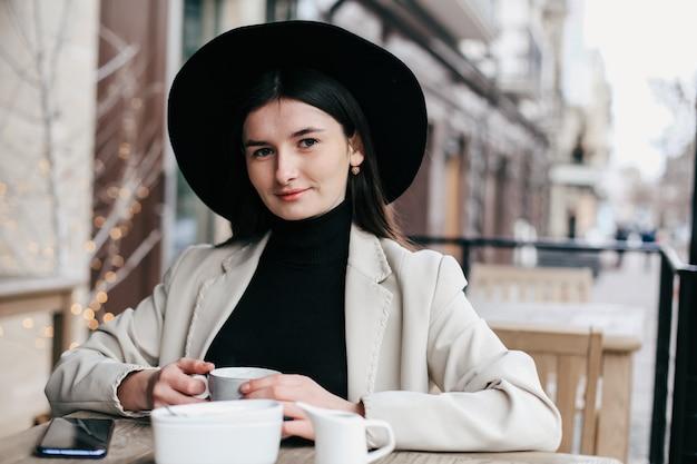 Mooie vrouw in zwarte fedora hipster hoed genieten van koffie in een koffieshop