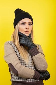 Mooie vrouw in zwarte handschoenen en hoed denken op geel.