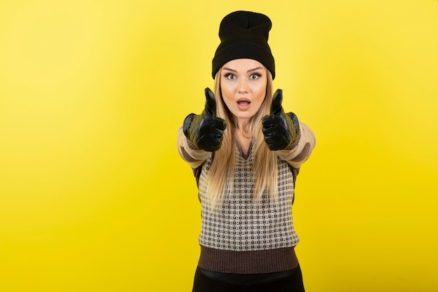 Mooie vrouw in zwarte handschoenen en hoed duimen opdagen.