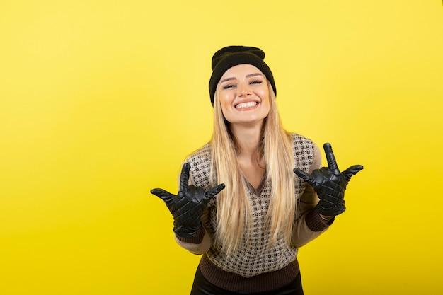 Mooie vrouw in zwarte handschoenen en muts die zich voordeed op geel.