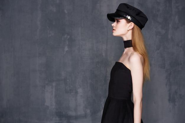 Mooie vrouw in zwarte hoed die kleding voor huismode verfraait