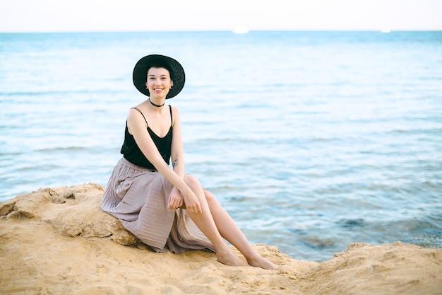 Mooie vrouw in zwarte hoed en overhemd zitten en glimlachen.