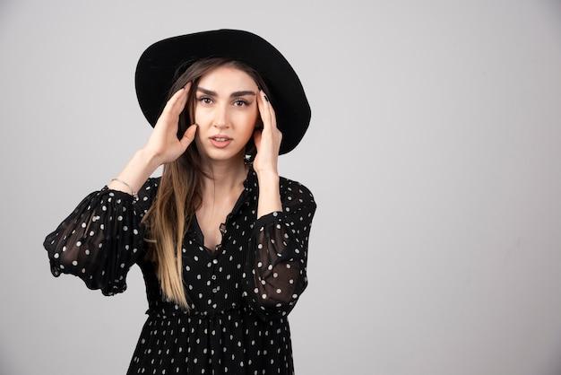 Mooie vrouw in zwarte hoed wat betreft haar gezicht.