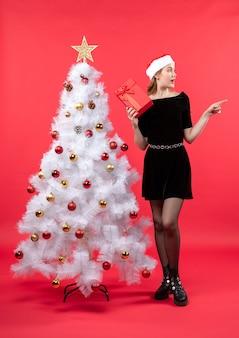 Mooie vrouw in zwarte jurk en kerstman hoed staande in de buurt van witte nieuwe jaar boom verrast