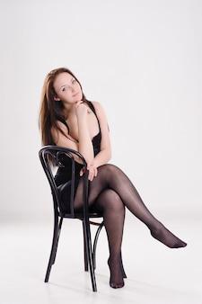Mooie vrouw in zwarte jurk geïsoleerd op wit