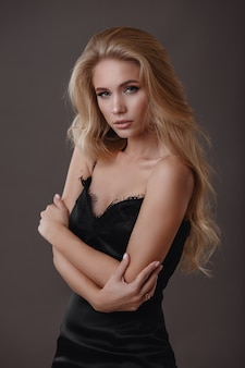 Mooie vrouw in zwarte jurk in de studio