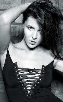 Mooie vrouw in zwarte jurk over bakstenen muur