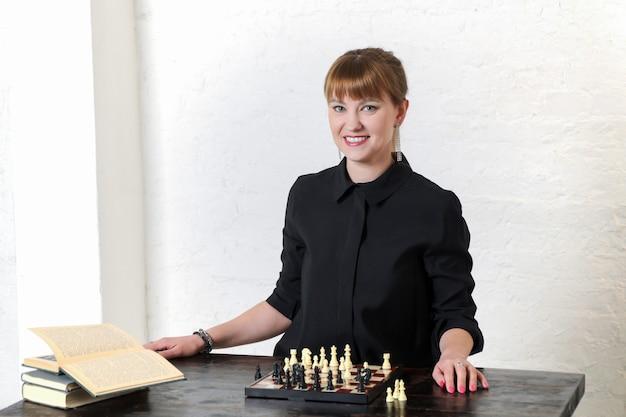 Mooie vrouw in zwarte jurk zit voor schaakbord en glimlacht
