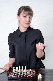 Mooie vrouw in zwarte jurk zit voor schaakbord, glimlacht en houdt een schaakpion in de palm van haar hand. concept studie schaak, vrouwen in schaaksport. verticaal beeld