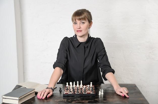 Mooie vrouw in zwarte jurk zit voor schaakbord