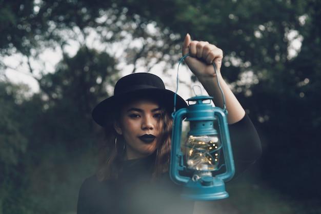 Mooie vrouw in zwarte kleding die zich in bos bevindt.