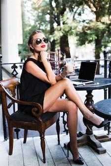 Mooie vrouw in zwarte korte jurk werkt aan tafel met laptop op terras in cafetaria. ze heeft het druk.