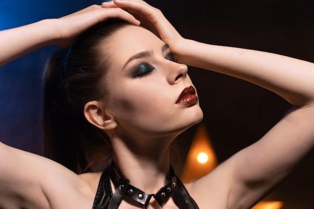 Mooie vrouw in zwarte lingerie en leren riem domineert de achtergrond van lampen en rook