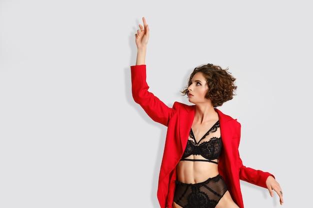 Mooie vrouw in zwarte lingerie en rode jas reiken (foto met kopie ruimte)
